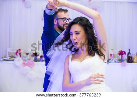 Happy newlywed couple having fun during their first dance at wedding reception - stock photo