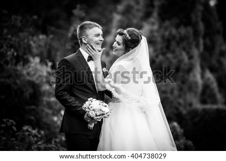 Happy newlywed couple hugging in park surrounded by trees