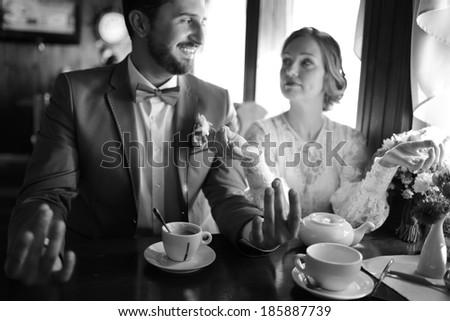 Happy newlywed couple in cafe. Groom and bride on wedding day.