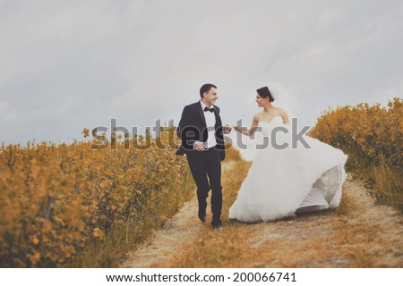 Happy newlywed couple in garden. Symbol of togetherness. - stock photo