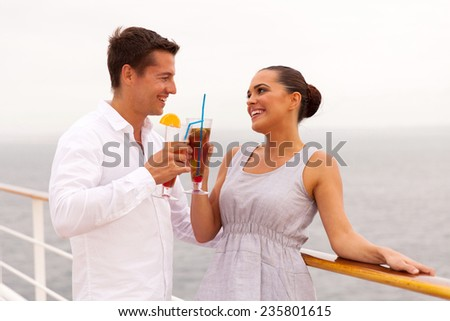 happy newlywed couple on honeymoon drinking cocktails on a cruise ship - stock photo