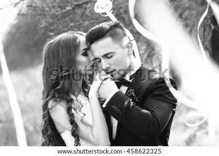 Happy newlywed couple posing and smiling in wedding dress and suit in forest decorated with ribbons outdoor, black and white