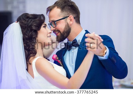 Happy newlywed couple smiling at their first dance at wedding reception closeup - stock photo