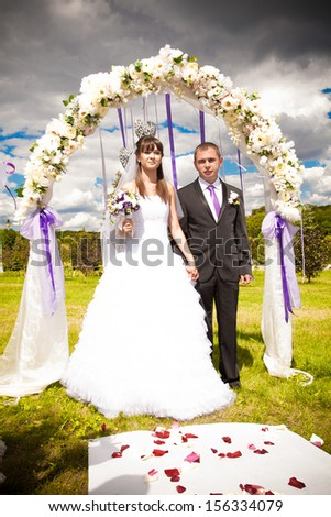 Happy newlywed couple standing in wedding arch - stock photo