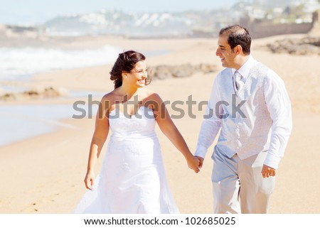 happy newlywed couple walking on beach - stock photo