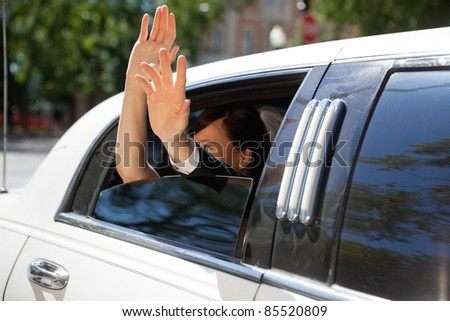 Happy newlywed couple waving out of limousine window - stock photo