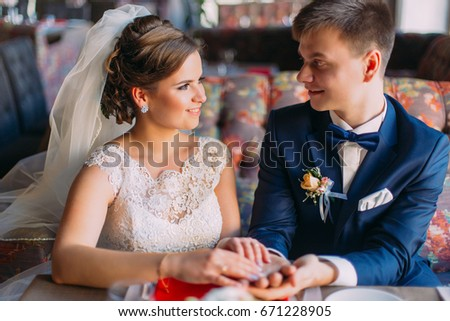 Happy newlywed enloved couple holding each other hands while sitting on sofa in restaurant