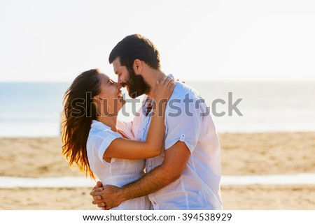 Happy newlywed family on honeymoon holidays - just married loving man and woman embracing  fun on sea sand beach. Travel lifestyle and people outdoor activity on summer vacation on tropical island. - stock photo