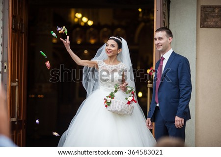Happy newlywed romantic couple coming out of church after wedding ceremony with a candy basket - stock photo