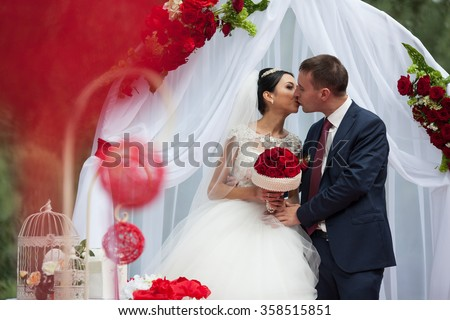 Happy newlywed romantic couple kissing at wedding aisle with red decorations and flowers - stock photo