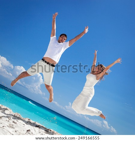 Happy newlyweds jumping up on beach with blue sky background - stock photo