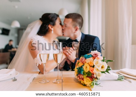 Happy newlyweds share a kiss drinking champagne in restaurant, celebrating the beginning of married life