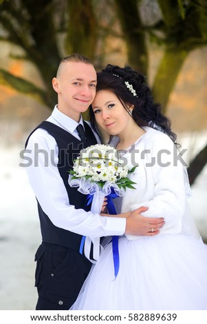 Happy newlyweds, wedding in the winter wood. The groom gently embraces the bride and smiles