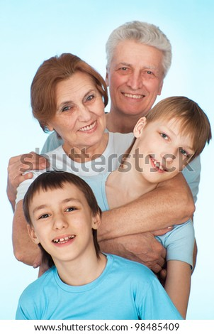 Happy nice Caucasian grandparents with grandchildren fooled on a light background - stock photo