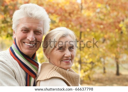 happy nice elderly couple in a autumn park - stock photo
