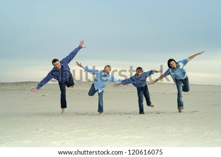 happy nice family playing on light sand - stock photo