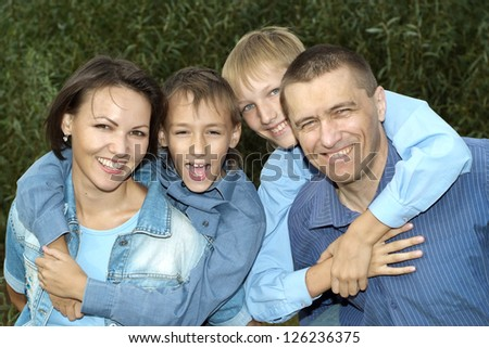 happy nice family posing outdoors in summer - stock photo