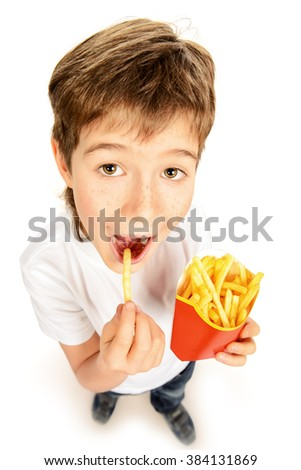 Happy nine year old boy eating french fries and smiling. Fast food. Concept of healthy and unhealthy food. Isolated over white. - stock photo