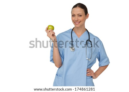 Happy nurse in scrubs holding green apple on white background - stock photo