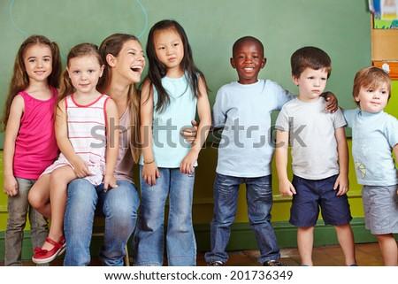 Happy nursery teacher with her group of children in a kindergarten - stock photo