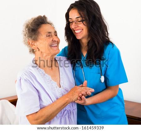Happy nurses keeping good mood in nursing home. - stock photo