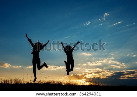 Happy of two women friends jumping and sunset silhouette with copy space. - stock photo