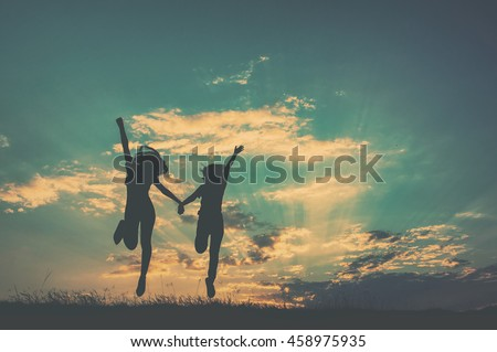 Happy of two women friends jumping and sunset silhouette with copy space.Vintage Tone