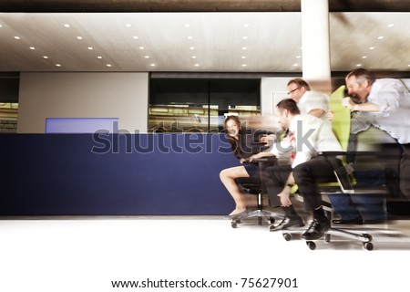 Happy office staff competing in an chair race and having a lot of fun, blue copy space area. - stock photo