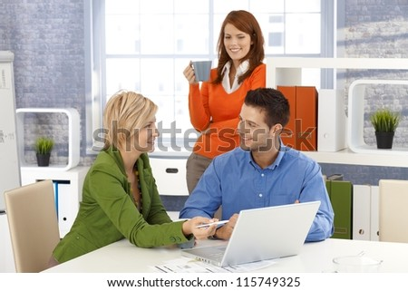 Happy office team at desk, discussing work, using laptop computer. - stock photo