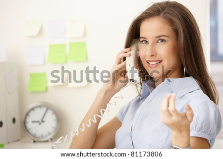 Happy office worker girl on landline call, smiling and gesturing.? - stock photo