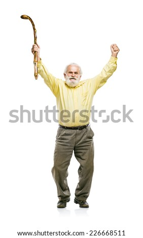 Happy old active bearded man jumping with cane in his hand isolated on white background - stock photo