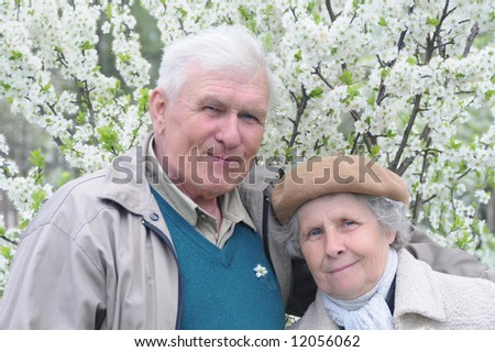 happy old couple against a background of flowering garden
