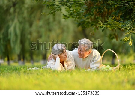 Happy old couple having picnic at the nature