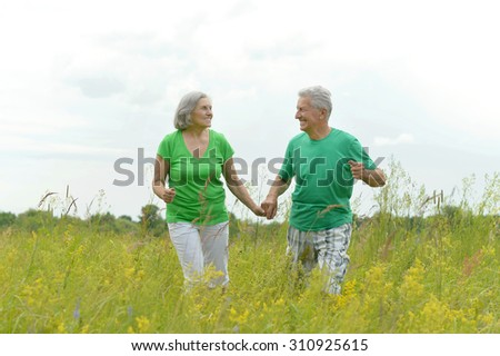 happy old couple playing at the nature - stock photo
