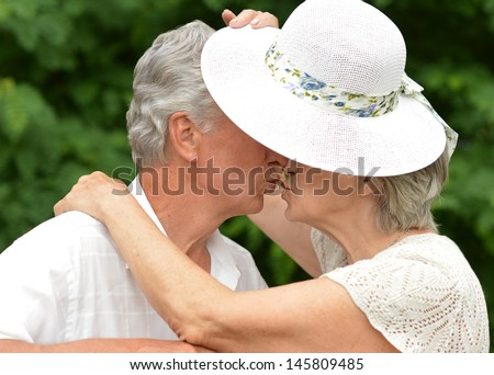 happy old couple walks in the park in summer day - stock photo
