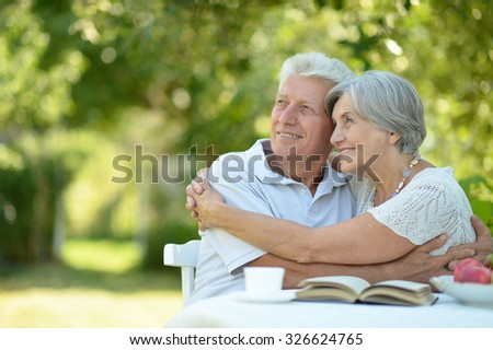 Happy old couple with drink and book in summer - stock photo