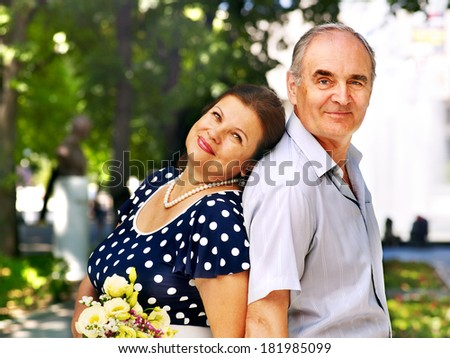 Happy old couple with flower back to back outdoor. - stock photo