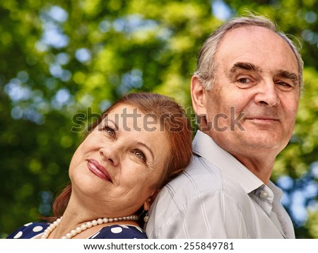 Happy old couple with flower back to backoutdoor.Loving eldery. - stock photo