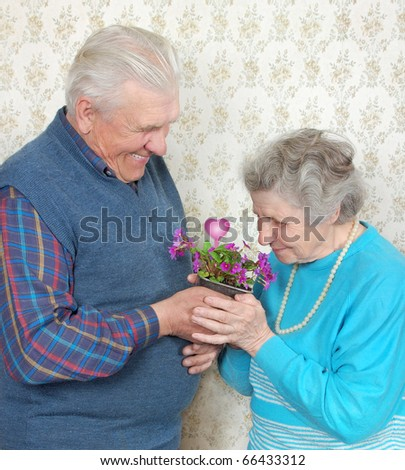 happy old couple with flowers and heart - stock photo