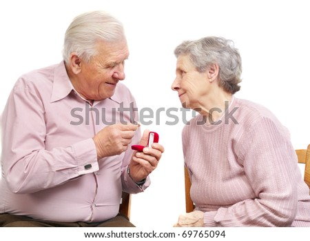 happy old couple with heart-shaped engagement ring on white background - stock photo