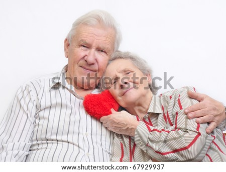 happy old couple with red heart on white background - stock photo