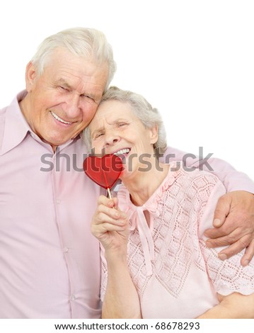 happy old couple with red heart-shaped candy on white background - stock photo