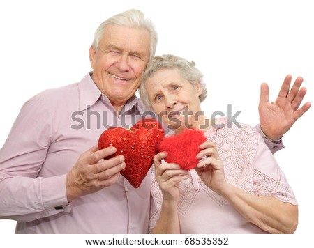 happy old couple with red hearts on white background - stock photo