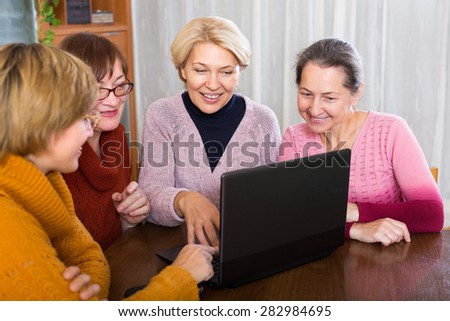 Happy old female  studying laptop  at home