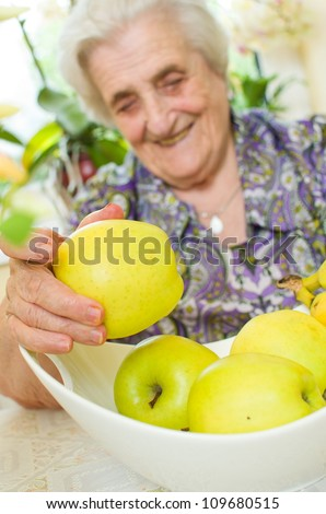 Happy old gray-haired woman with fruits - stock photo