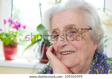 Happy old gray-haired woman with glasses