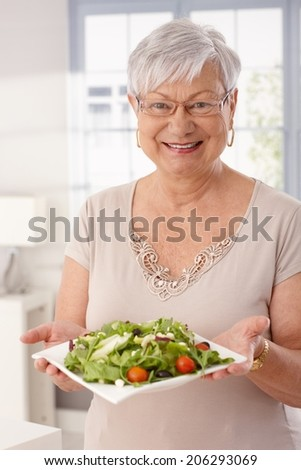 Happy old lady holding plate of fresh green salad, looking at camera. - stock photo