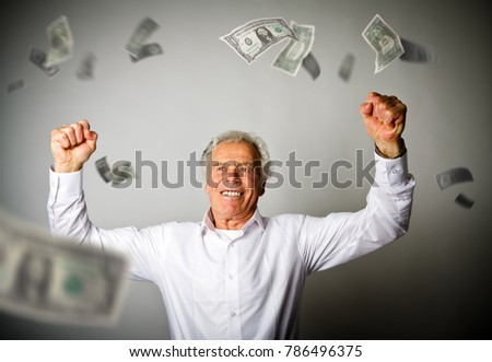 Happy old man in white and falling dollar banknotes. Currency and lottery concept.