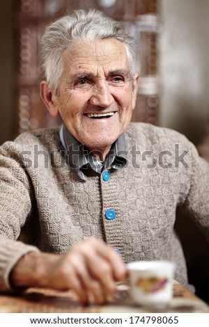 Happy old man indoor having his morning cup of coffee