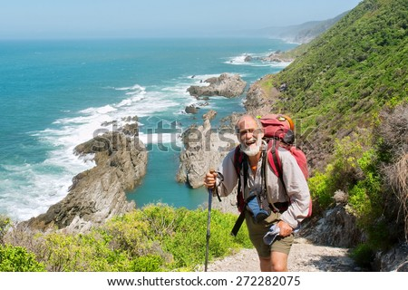 Happy old man just reaches the top of hill. Shot on the Otter trail in the Tsitsikamma National Park, Garden Route area, Western Cape, South Africa.  - stock photo
